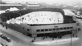Aerial image of a stadium with a snow-covered ground and packed stands