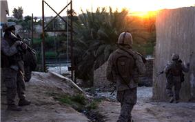 A squad of Marines patrolling through houses and palms trees with a river in the background.