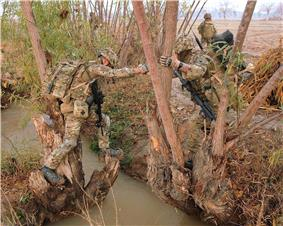 Colour photograph of two marines climbing over a tree-lined, water-filled ditch.