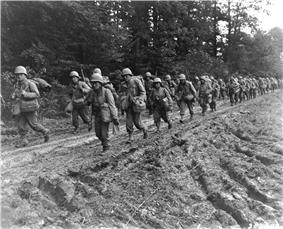 Two columns of Japanese American soldiers in route step in France.