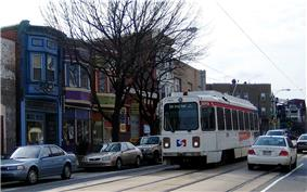 A white single-car trolley in street running. On street parking combined with double track on a two-lane street leaves limited room for automobile maneuverability.
