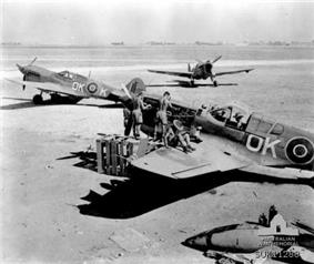 Several men in shorts working on a single-engined fighter plane; two other fighters are parked a short distance away