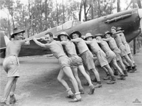 Nine men wearing shorts, seven of them wearing wide brimmed hats, push a propeller-driven aircraft.