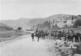 Mounted troopers in the foreground and another group in the middle distance on a road winding between high hills