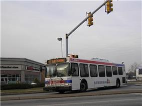 A white bus passes through an intersection.
