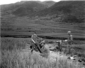 Men stand around a mortar high on a mountain
