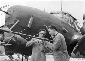 Ground crew adjust a No. 67 Squadron Avro Anson's radar in 1945
