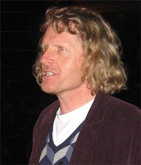Grayson Perry, a man wearing a corduroy jacket who is looking to his right