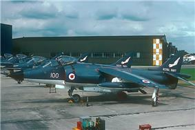 Line-up of Sea Harrier jet aircraft, facing left of photograph. In the distance is a tall, dull-coloured warehouse.
