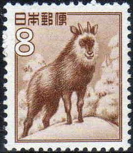 A postage stamp featuring a sepia illustration of a goat-antelope standing on a snow-covered, forested hilltop.  Stylized Japanese writing in the top left corner reads: