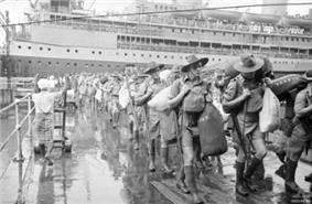 Men in shorts and slouch hats with rifles slung, carrying duffel bags march along a wharf. In the background is a cruise ship.