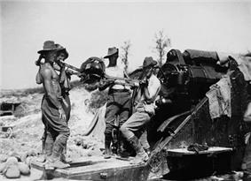 Bare chested men in slouch hats and breeches stand by a large artillery piece, ready to load a shell