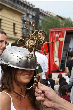 smiling woman wearing a colander on her head being