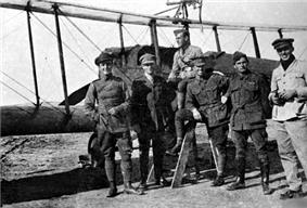 Full-length outdoor portrait of six men in military uniforms in front of a military biplane with a machine gun mounted on the upper wing