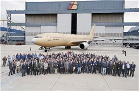Crowd of people assembled in front of unpainted aircraft. A tall building serves as the backdrop for the photograph