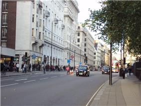 A street view of Piccadilly, showing buildings, two London taxis and a bus
