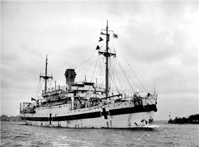 A single-funnelled merchant ship at rest. The ship is painted white, with a dark horizontal band along the hull, interspersed by dark crosses. The number