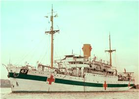 A single-funnelled merchant ship at rest. The ship is painted white, with a dark green horizontal band along the hull, interspersed by three red crosses. The number