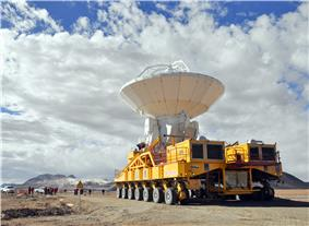 Large white parabolic-dish antenna on yellow, multi-wheeled vehicle