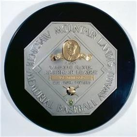 A black circle with an octagonal silver plaque in the middle. The edge of the plaque reads