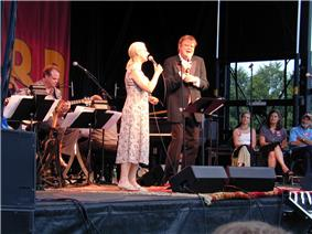 Full length portrait of young woman wearing a sleeveless dress on left, blond hair pulled back into ponytail, and middle aged male wearing a brown tuxedo on right, in brown longish hair, singing into microphones. Three people seated at right listening, guitar player visible in band at left.