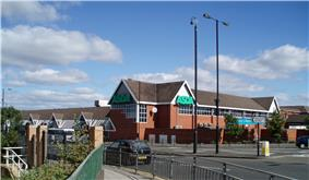 A 1980s medium-sized supermarket building, viewed from across the Great North Road
