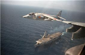 A Harrier flies over an aircraft carrier below