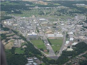 Aerial photograph showing a large industrial area, including a number of laboratory buildings (some with chimneys), roadways, and recreational areas