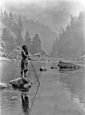 Photo of man standing on rock holding spear with spearpoint in the water