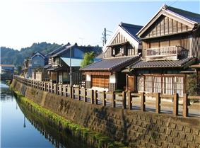A small street and wooden houses next to a canal.