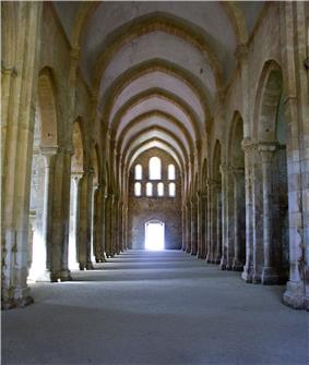 A corridor enclosed by large pillars, which ends with a small doorway.