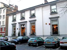 A number of cars are parked in the asphalt car-park of a two-storey white building.  The building appears once to have been detached, but a two-storey extension is apparent, on the right side of the building.  The ground floor contains three large sash windows, each with a small metal railing around the sill.  The first floor contains four shorter sash windows.  The decorative stonework around the windows and main entrance has been painted grey.  Two chimney stacks are visible on the roof, at opposite ends.  The staircase entrance to the building is bordered by metal railings.  To the left of the image, a much larger brick building can be seen in the distance.