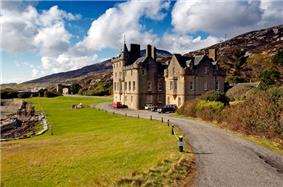 A large mansion house in the Scottish baronial style of the 19th century sits at the end of a narrow driveway with the shore on the left and moorland to the right.