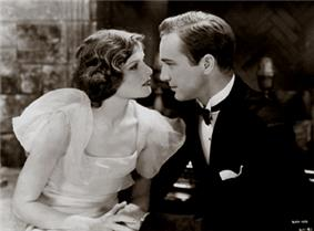 Hepburn and a young man acting in A Bill of Divorcement. They are holding hands and looking at each other emotionally.
