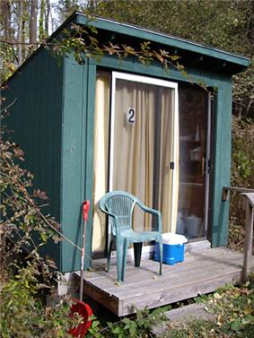 Photo of a small lean-to style wooden hut with a sliding glass front door.