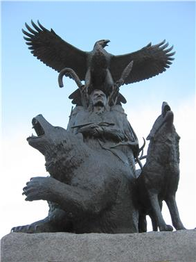 A life-sized bronze statue of an Aboriginal and eagle above him; there is a bear to his right and a wolf to his left, they are all looking upwards towards a blue and white sky