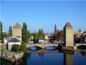 A pair of rectangular medieval stone towers guard both banks of a river and the stone bridge that stretches between them.