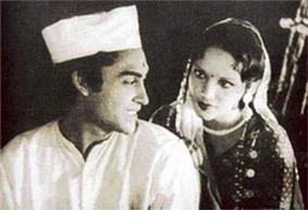 Ashok Kumar is looking back towards Devika Rani in a black and white still shot from a film.
