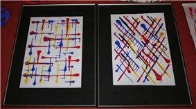 Two paintings (portrait orientation) are side-by-side with the only marks being thick lines that terminate with a sizeable dot of blue, yellow, or red. The left one has lines vertical/horizontal and he right one has lines diagonally.