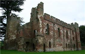 A ruined building minus a roof and with crumbling walls. Some of the walls are crenelated. The walls are build with red stones in the middle and grey stones as edging on the tops and corners.