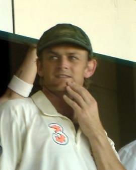 A man in a white cricket shirt and a baggy green cap, with his left hand on his chin, looking to his right