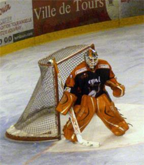 An ice hockey player standing partially crouched in goals. He is wearing a helmet, gloves and leg pads and a black and orange uniform.