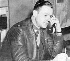 Profile of a white man leaning forward with a large phone handset pressed to his ear. He is wearing a leather jacket over a shirt and tie.