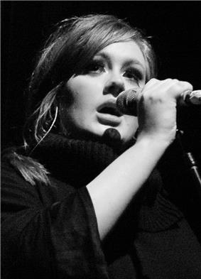 Black-and-white photo of a woman holding a microphone.
