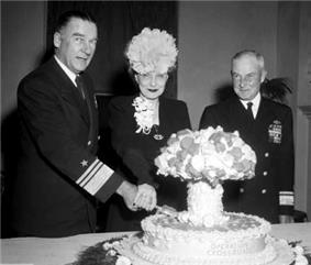 A man in naval uniform and a woman wearing a hat cut into a cake labeled Operation Crossroads, and shaped like a mushroom cloud, while another naval officer looks on.