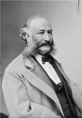 Back and white photo of a bearded man wearing a suit and a bow tie looking right