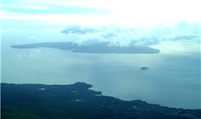 Photo showing large island (Kahoʻolawe) mostly covered by cloud, and the smaller islet of Molokini with the South Maui coast in the foreground