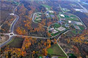 An aerial view of a school campus in a wooded area. The trees around the campus have red leaves. Roads cut through the middle of the wood toward the school.