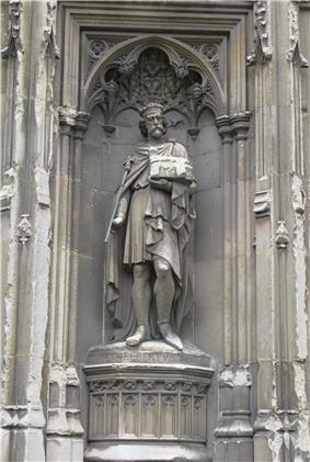 Stone statue of a crowned man holding a sceptre.