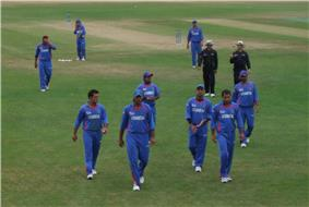 Nine men in a field wearing a blue outfit. Two men wearing a black outfit, along with a cricket pitch in the background, can be seen.